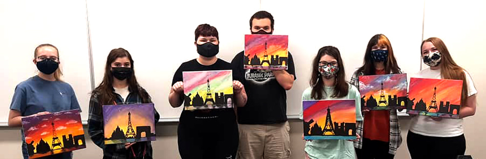 french ba program student club students holding paintings of Eiffel tower